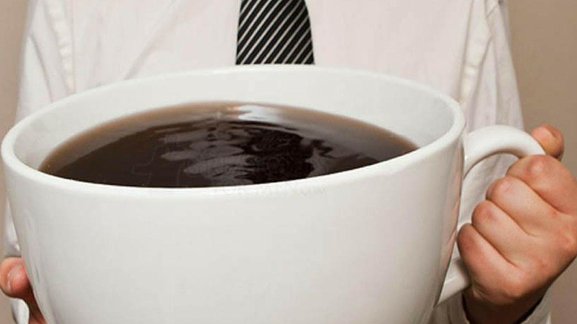 un uomo con una tazza enorme piena di caffè