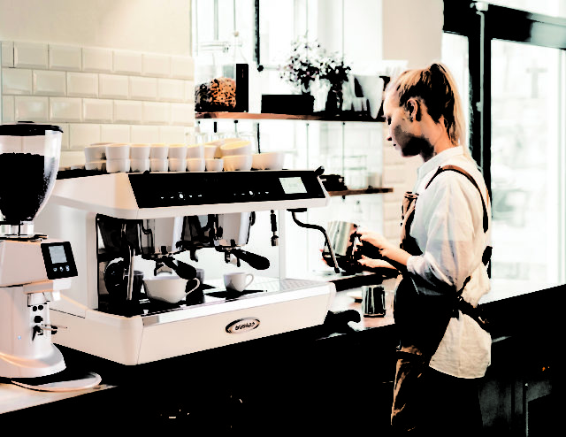 Female barista using coffee machine at cafe