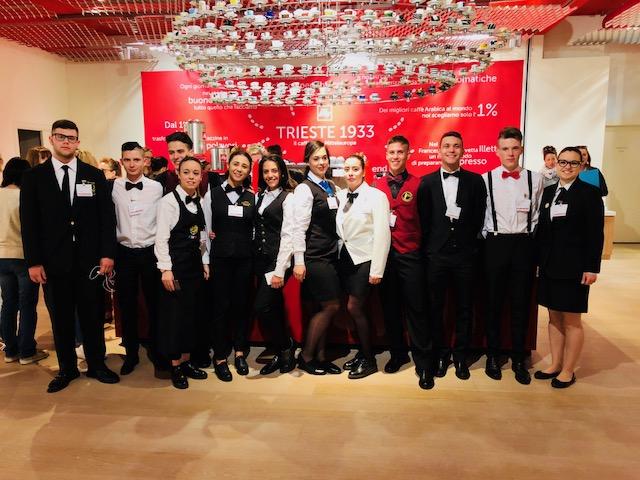 I 16 consorrenti alla finale del concorso maestri dell'Espresso Junior sotto la collezione delle tazzine illy