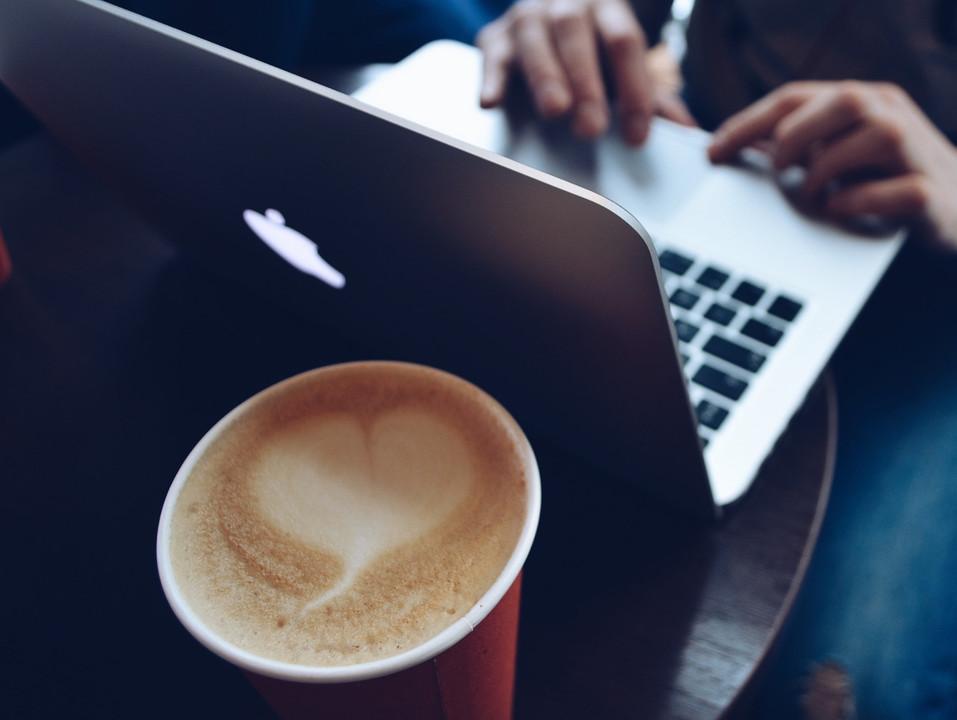 Una classica immagine di una caffetteria Strabucks: computer e cappuccino con tanto di latte art