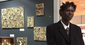 Il giovane artista gambiano Abdoukhadre Ba e, sullo sfondo, alcune delle sue opere
